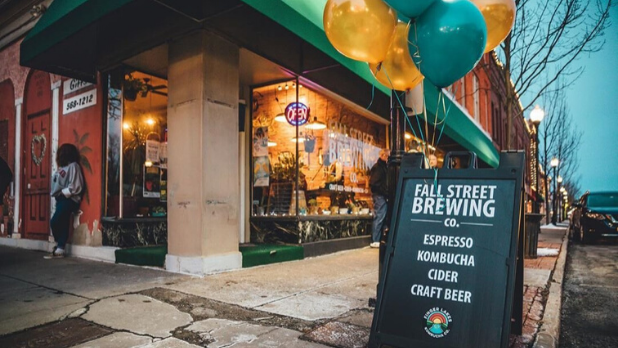 A photo of the Fall Street Brewing sidewalk sign that says: espresso, kombucha, cider craft beer, with green and yellow balloons floating from the top