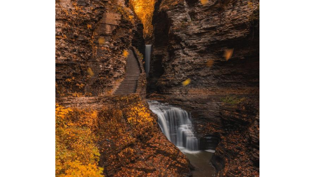 Watkins Glen State Park trail during the fall season with orange leaves and a waterfall