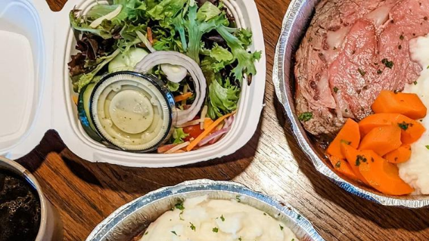 Salad in a takeout container with mashed potatoes, carrots and slow roasted prime rib