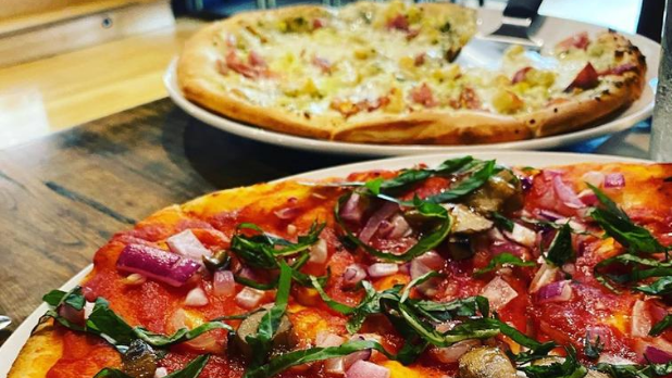 Two pizzas on a table from Dina's Restaurant