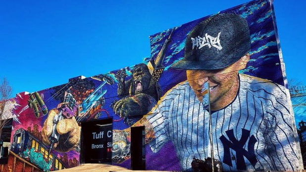 A street mural on the side of TuffCity Tatto in Bronx showing a tattooing Yankee artist