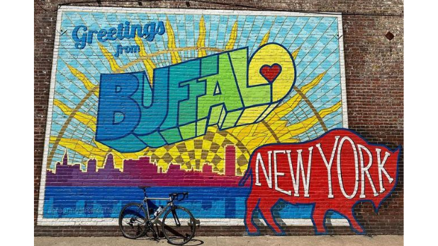 "A colorful mural that says ""Greetings from Buffalo"" with the words ""New York"" written on a red buffalo"