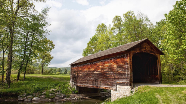 The wood brown Hyde Hall covered bridge in the forest