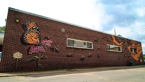 A painting of a Monarch butterfly and bees pollinating flowers on the side of the Narrowsburg Post Office