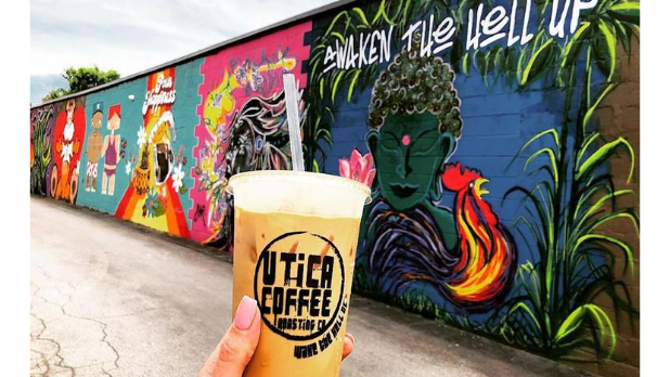 A girl holding an iced coffee with colorful murals in the backgroun at Utica Coffee Roasting Co.