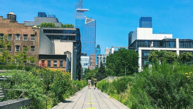 A sunny day on The High Line with two people walking in the distance