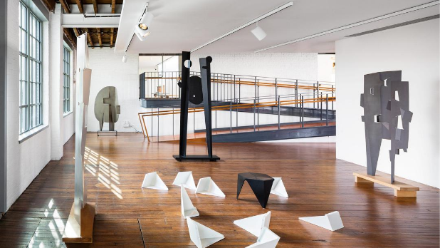 A display of white sculptures on the ground and tall black sculptures at The Noguchi Museum