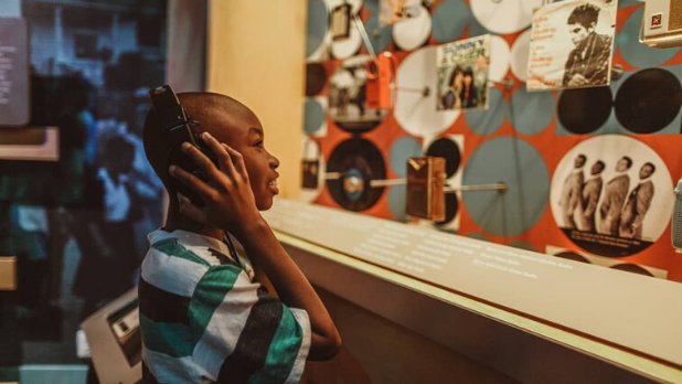 A little boy with headphones on listening to an exhibit at Bethel Woods