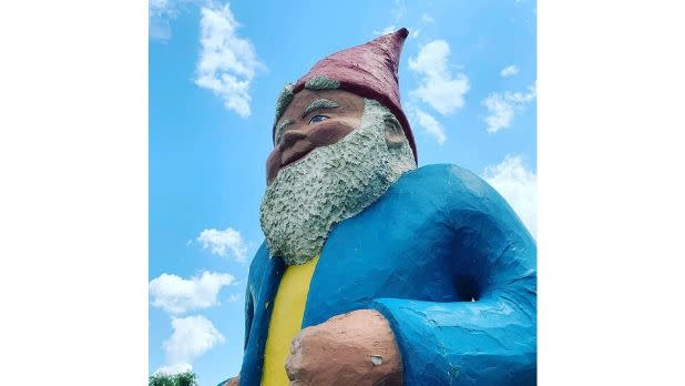 A giant garden gnome with a red pointy had, yellow shirt and blue jacket
