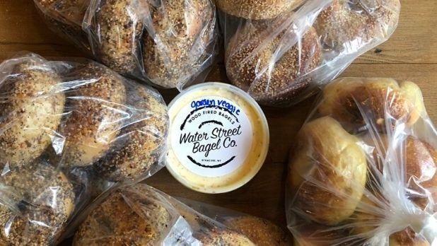 "An photo of a cream cheese container that says ""water Street Bagel Co."" surrounded by bags of bagels"