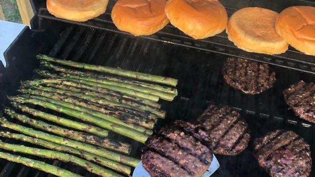 Asparagus, Butter Meat Co. burgers and buns on grill