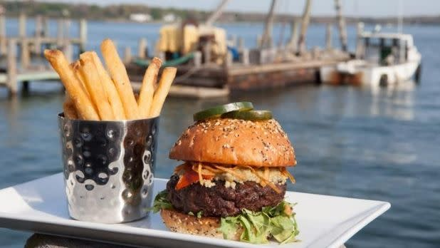 A burger and fries pictured on the waterfront with a boat in the background