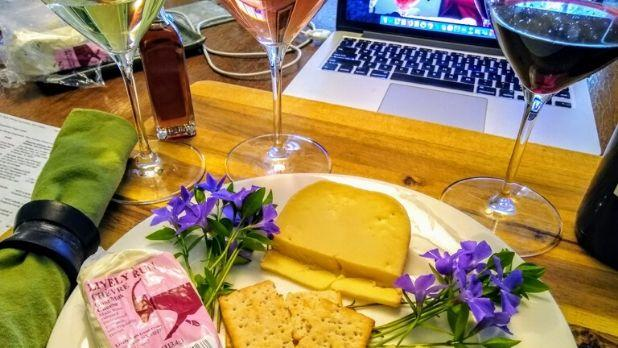 A plate of cheese and crackers with glasses of wine nearby