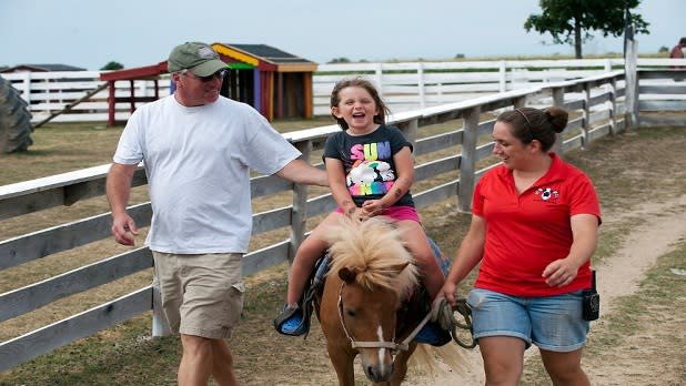 Little girl rides a pony at Old McDonald's Farm in Sackets Harbor, NY