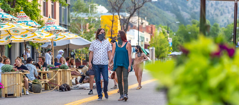 Man and woman walking with masks along Downtown Boulder Patios