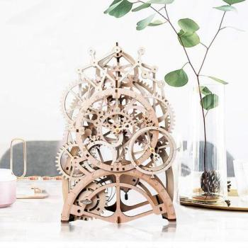 A mechanical clock kit made of laser cut wood is displayed on a table.