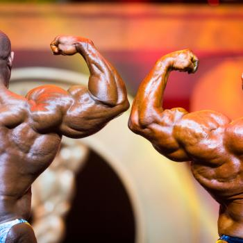 Rear view of two bodybuilders flexing their arms in the Arnold Sports Festival