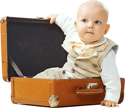 Photo of a young toddler wearing a beige suit sitting up in a suitcase.