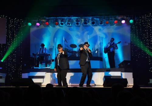 Two men in suits, hats, and glasses sing and dance with a live band on a blue lit stage