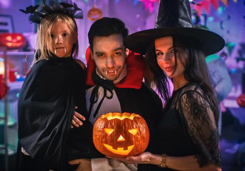 A family dressed as vampires, and a witch with a jack o lantern