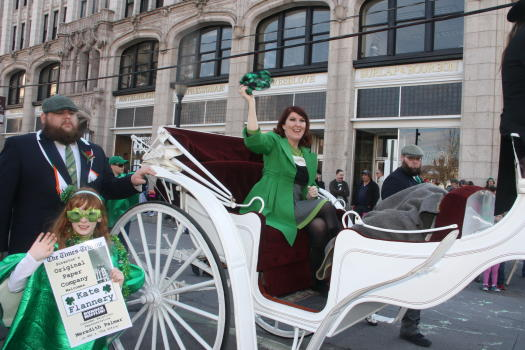 St. Patrick's Day Parade participant wearing a green dress and riding in a white carriage waves to the crowd