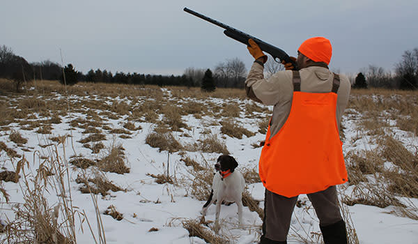 Hunter wearing reflective gear aiming shotgun in the air with his trusty dog in the snow