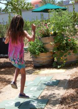 Girl doing hopscotch at the Farm Food Lab in Irvine, CA