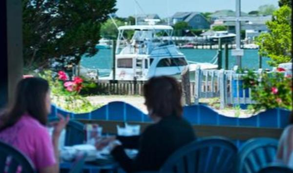 People dining at South Beach Grill overlooking the Banks Channel in Wrightsville Beach, NC