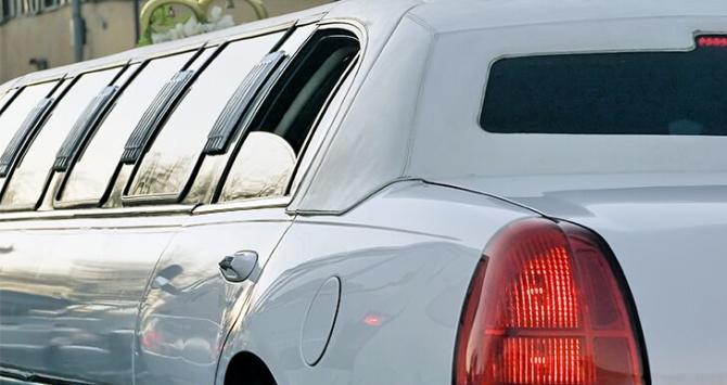 A white limo viewed from the rear with the rear driver-side window down halfway
