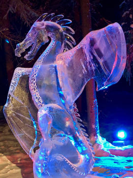 close up of a lighted large dragon carved from clear ice