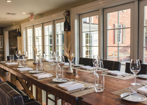An elegant table setting with windows in the background at the Brick Farm Tavern