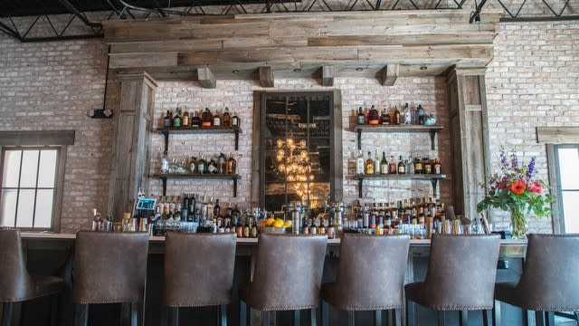 Seneca bar area with stools lined up in front of bar and exposed brickbehind the bar with shelving and bottles