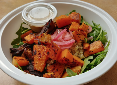 A Grain Bowl from Invoke is topped with quinoa, arugula, sweet potato & pickled radish.