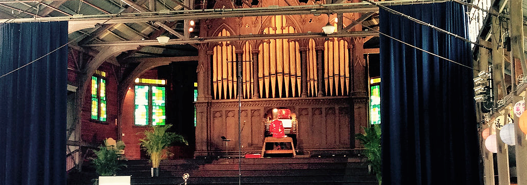 Man sitting at the large organ on stage with his back to the audience