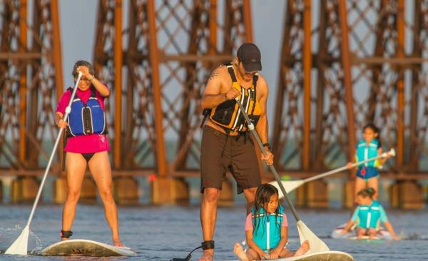 5 people paddle-boarding on a body of water