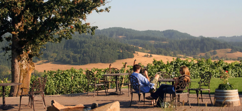 Couple sits at a table on a terrace at Sweet Cheeks Winery overlooking wine country.