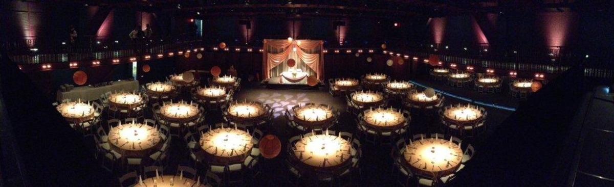 a dark room featuring tables and paper lanterns