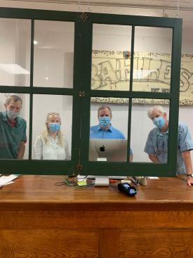 Bahle's used vintage windows instead of plexiglass to add a (creative, eye-catching!) layer of protection for customers and staff.  From left to right: Rich Bahle, April Gilbert, Chris Hufford and Chris Bahle