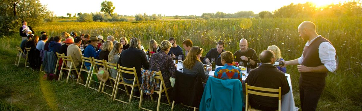 People sitting at a long rectangular table during a Boulder Farm Dinner