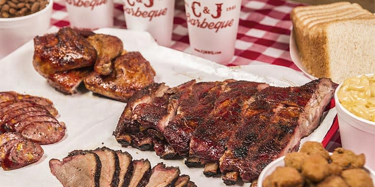 C&J BBQ plate of ribs, brisket, bbq chicken, toast and sides on a red and white table cloth