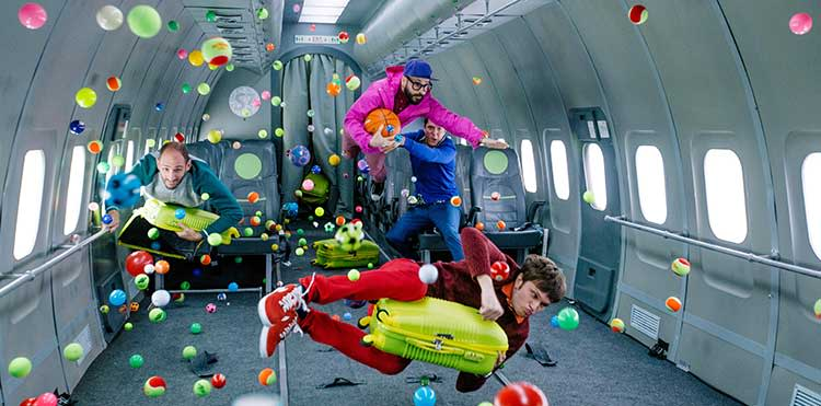 Colorful balls and four men floating in zero gravity on a plane