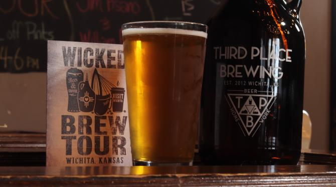A full pint of beer, a growler, and a table-top sign sit on the bar at Third Place Brewing. The sign includes details for the 2019 Wicked Brew Tour in Wichita.