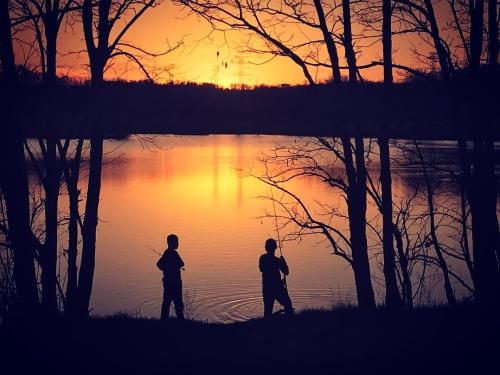 People fishing at sunset of Sam Peden Park