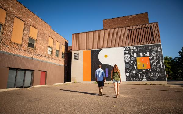 Couple looking at Bon Iver Mural in Downtown Eau Claire