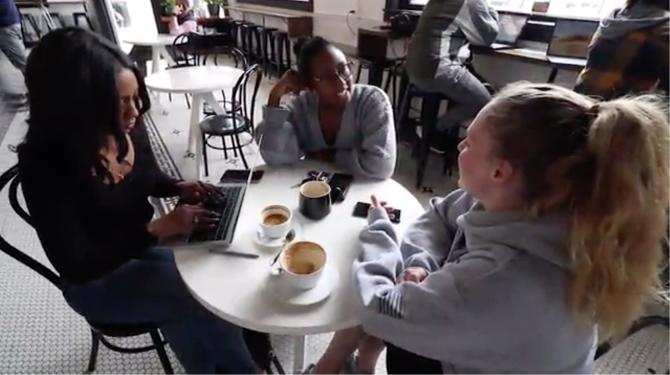 Three girlfriends sit around a table and chat at Leslie Coffee Co