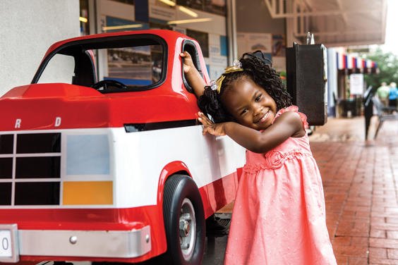 Image of a happy young girl leaning against a a coin operated replica of Sam Walton's truck