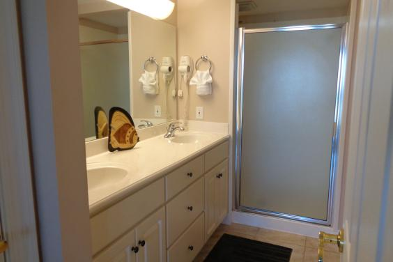 Master bath with marble vanities, dual shower heads, private commode, walk in closet