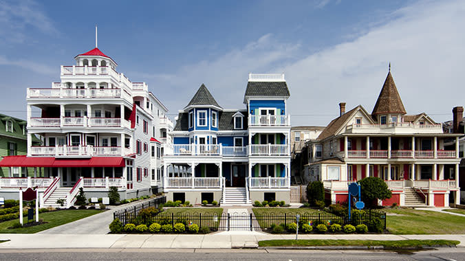Images of three, large properties in Cape, May New Jersey. One property is red, another is blue, and the final one is brown.