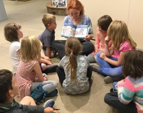 a woman reads a story to children