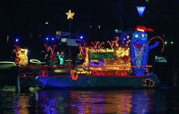 "Island of Lights Flotilla lit up with sign that says, ""Carolina Beach Fishing Pier"""